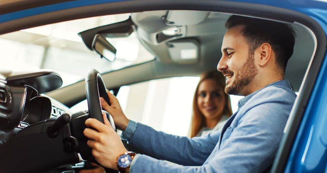 Young couple choosing new car for buying in dealership shop